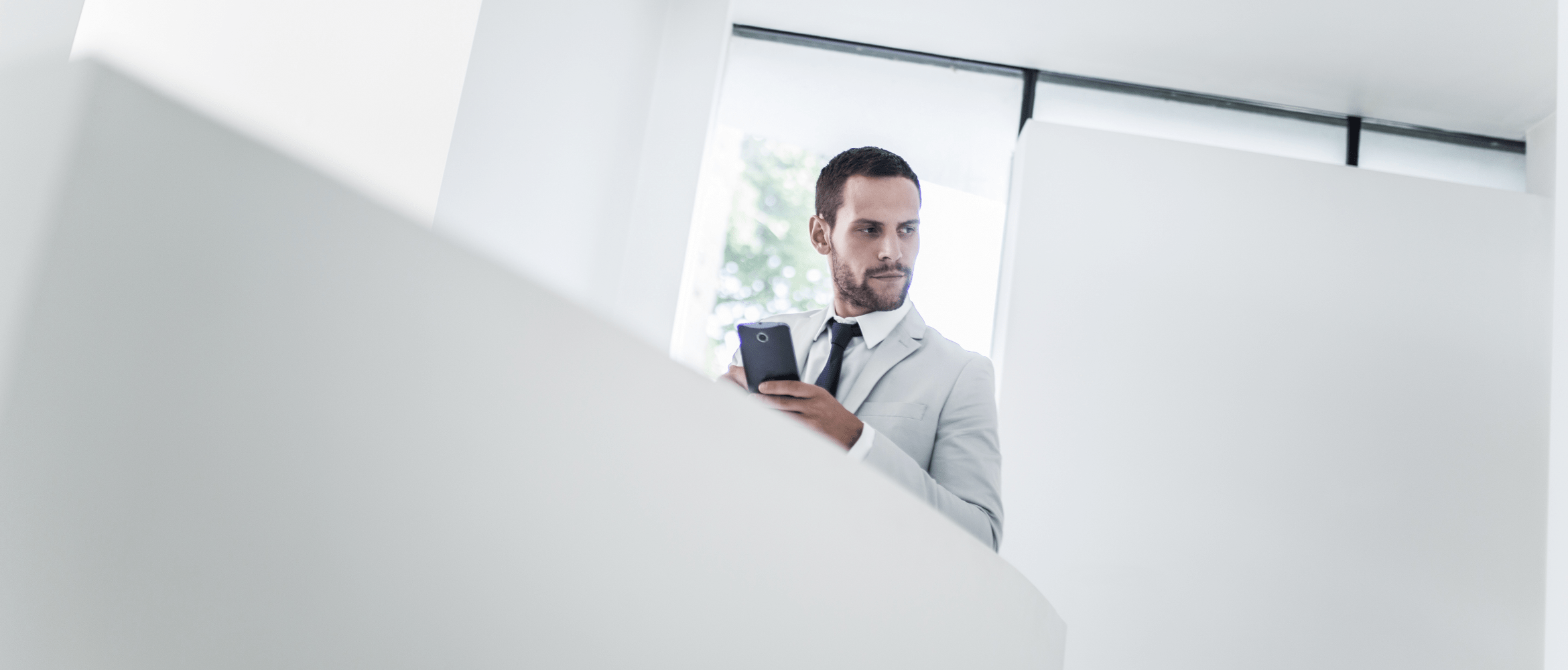 Man in a white suit with Android smartphone overlooking balcony