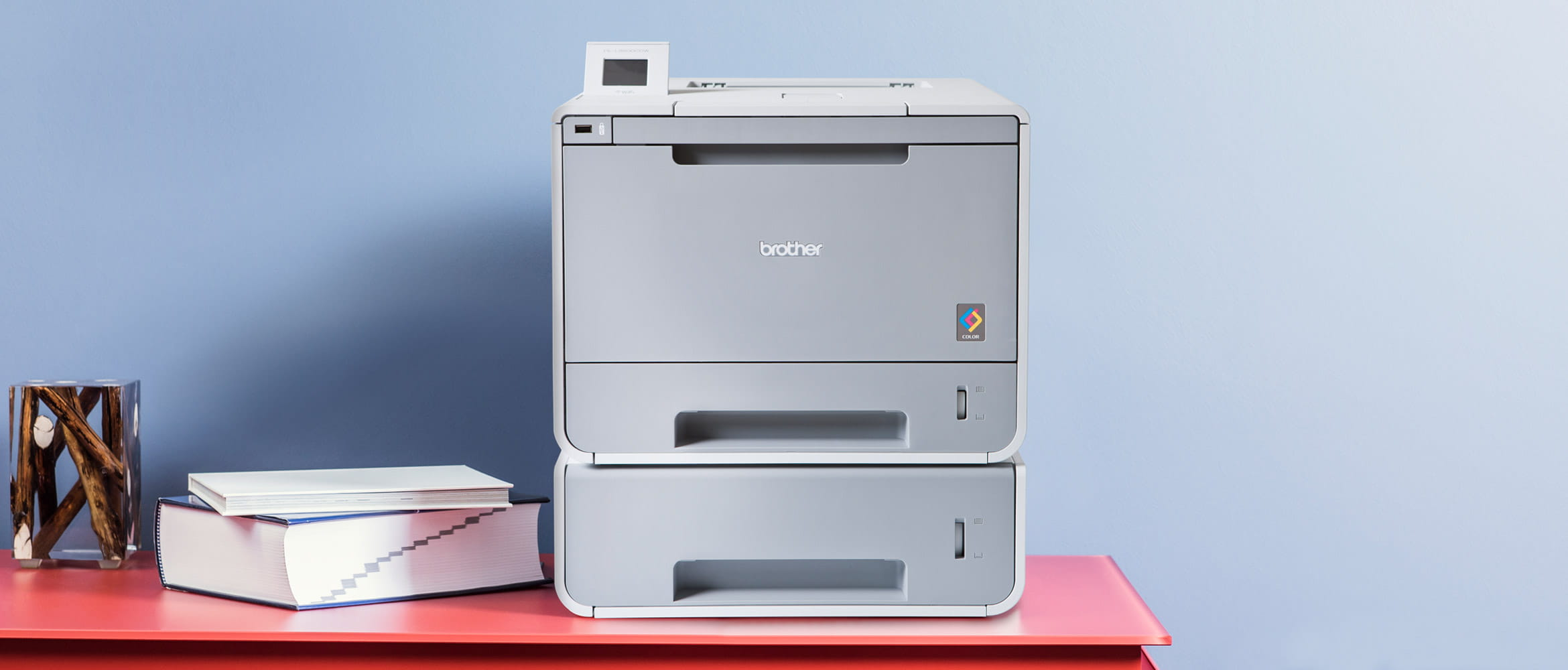 Brother Colour Laser Printer next to office supplies on a red desk
