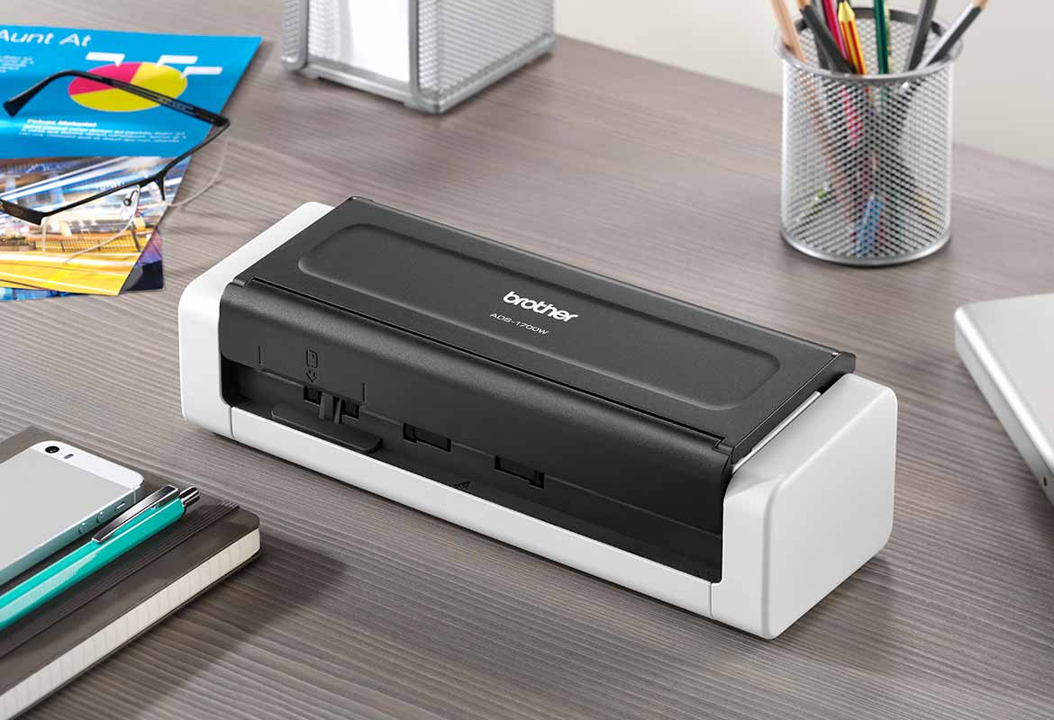 Brother ADS-1700W compact document scanner closed on grey desk