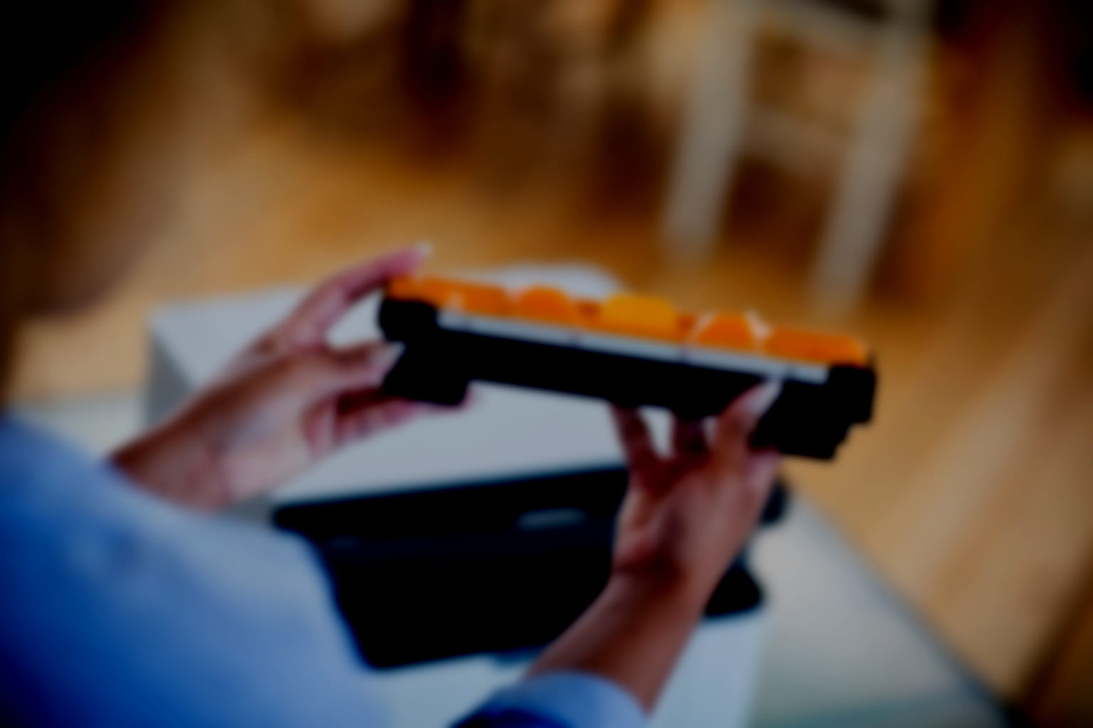 A woman holds a Brother printer toner cartridge - the image is blurred