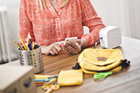 A mother using a Brother P-touch Cube to print labels for the contents of her child's school bag
