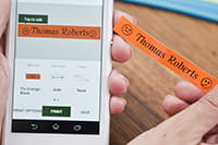 """Someone using a smartphone to print an orange label with the words """"Thomas Roberts"""""""