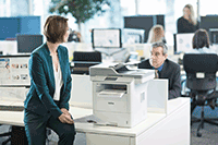 Women in green jacket sat on desk with professional 3 in 1 mono laser printer