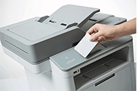 Close up of 3 in 1 printer, with hand holding ID card