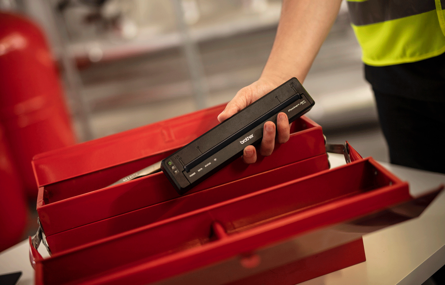 Workman putting black pj printer in red worbox