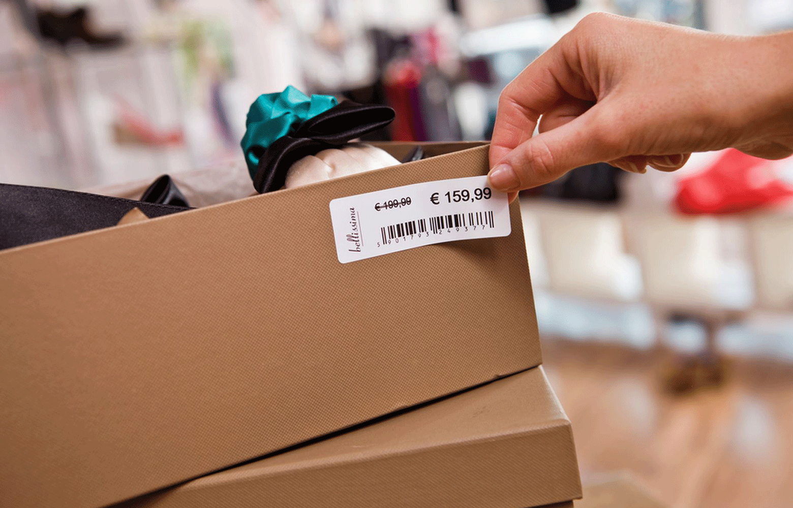 Brown shoe box being labelled with price label