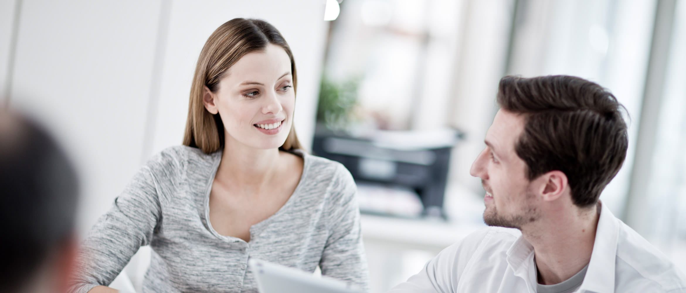 Man and women in front of laptop are smiling, printer in the background