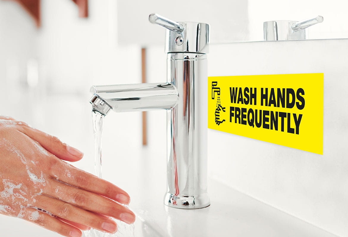 hands being washed with label visible on the splash back