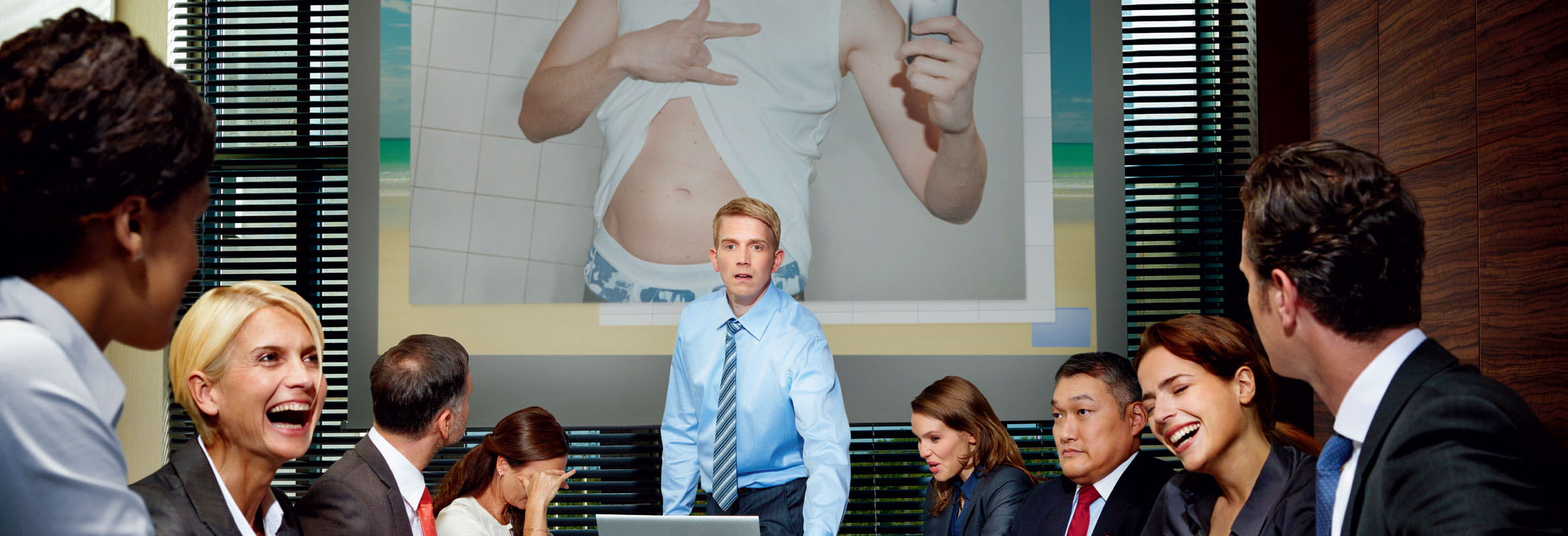 People laughing at office presentation
